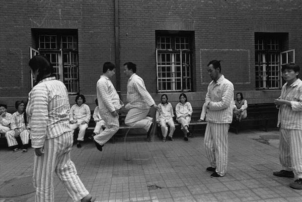 Les activités de plein air sont limitées dans ce centre psychiatrique de Pékin. Les patients se promènent, s'assoient, et certains s'amusent à sauter. ©Lu-Nan / Magnum Photos
