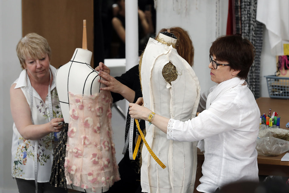 Chanel seamstress staff members work on the catwalk background as part of Chanel's Haute Couture Fall-Winter 2016-2017 fashion collection presented Tuesday, July 5, 2016 in Paris. (AP Photo/Francois Mori)
